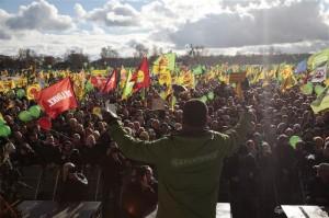 Záběr z té klidnější, městské části demonstrace. V popředí jsou vidět záda výkonného ředitele Greenpeace International Kumiho Naidooa, kterak promlouvá k davu.