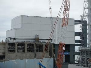 Dokončené stěny a střecha krytu čtvrtého bloku výrazně kontrastuje s budovou poškozenou výbuchem vodíku. Stav k 20. červenci 2013. (Zdroj: Tepco.co.jp)