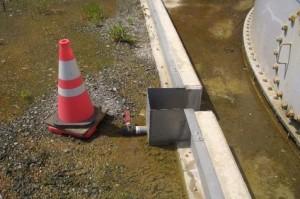 Výpusť pro dešťovou vodu, kterou unikla kontaminovaná voda za ochrannou hráz, která se rozkládá kolem protékající nádrže. (Zdroj: Liberation.fr)