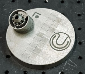 Výroba součástky pro letecké motory GE pomocí 3D tisku. Vlevo hotová součástka těsně pře odřezáním z desky, vpravo pouze první vrstva. Zdroj: MIT