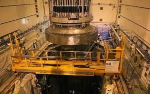 Víko je opatrně spouštěno na reaktorovou nádobu. Víko bude potřeba sejmout znádoby až při jejím plnění palivem. Jakmile bude znovu umístěno, bude připevněno ktlakové nádobě 52 šrouby. (Zdroj: World Nuclear News)