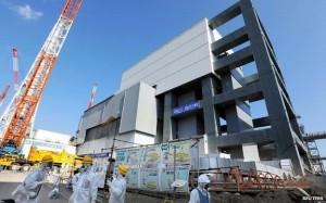 Kryt nad budovou čtvrtého bloku fukušimské jaderné elektrárny byl dokončen teprve nedávno a již se připravuje splnit svůj účel. Svým zařízením, jako je jeřáb a filtrační a ventilační soustava, umožní bezpečné vyjmutí paliva z bazénů. (Zdroj: Bbc.co.uk)