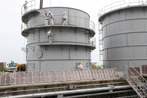 Pracovníci rozebírají jednu ze šroubovaných nádrží, které má společnost TEPCO v plánu nahradit svařovanými, u nichž je nižší riziko úniků vody. (Zdroj: Japantimes.co.jp)