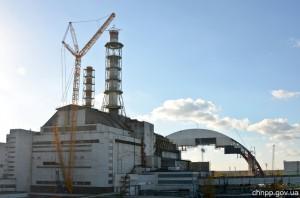 Zvedání vrchní části ventilačního komínu. V pozadí můžete vidět nový sarkofág, který bude koncem roku 2015 přesunut nad reaktorovou budovu. (Zdroj: Chernobylfoundation.org)