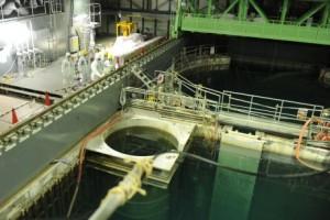 Technici v novém úkrytu. Prázdná aktivní zóna se nachází pod kruhovou částí, pod čtvercovou je skladovací bazén. Zdroj: WNN