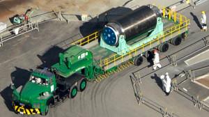 Odvoz kontejneru s 22 palivovými kazetami z poškozené budovy do jiné, kde bude moci být bezpečně skladováno. (Zdroj: Rt.com)