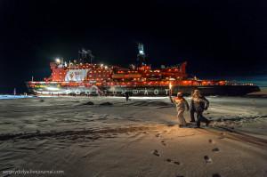 Fotografie z návštěvy Severního pólu s olympijskou pochodní. Těsně před trupem je ukazatel vzdáleností umístěný v místě severní točny. (Zdroj: Olympdep.ru)