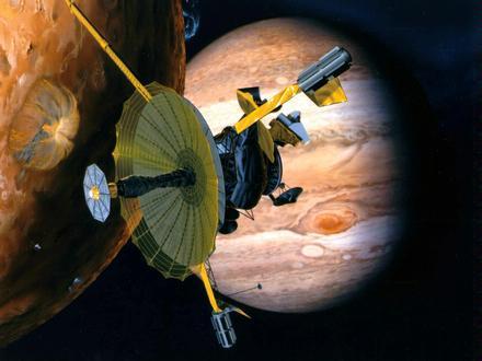 Planetární sonda Galileo, která jako první v historii zamířila k Jupiteru a jeho měsícům. Na této umělecké představě můžete v pozadí vidět Jupiter a větší část obrázku zaplňuje jeho měsíc Io se svými vulkány. (Zdroj: Jpl.nasa.gov)