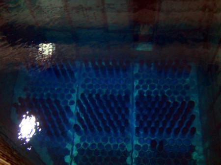"""Palivové kazety se """"svatozáří"""" Čerenkovova záření ve skladovacím bazénu. Bazén má dvě patra a ve spodním jsou kazety naskládány těsněji na sebe. (Zdroj: Atominfo.cz)"""