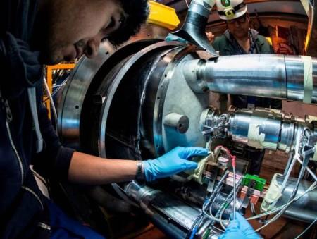 Technik s pomocí zrcátka kontroluje správné umístění nové spojky mezi supravodivými magnety.